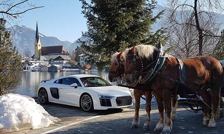 Audi R8 with snow and a horse-drawn carriage at the foothills of the Alps.